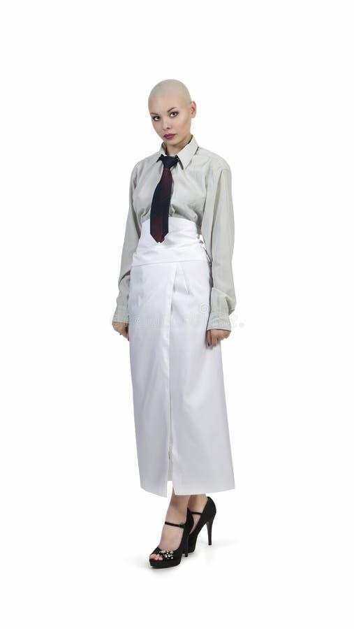 Emocjonalny portret dziewczyna, ogolony łysy, w lekkiej koszula z krawatem i białą spódnicą zdjęcie royalty free