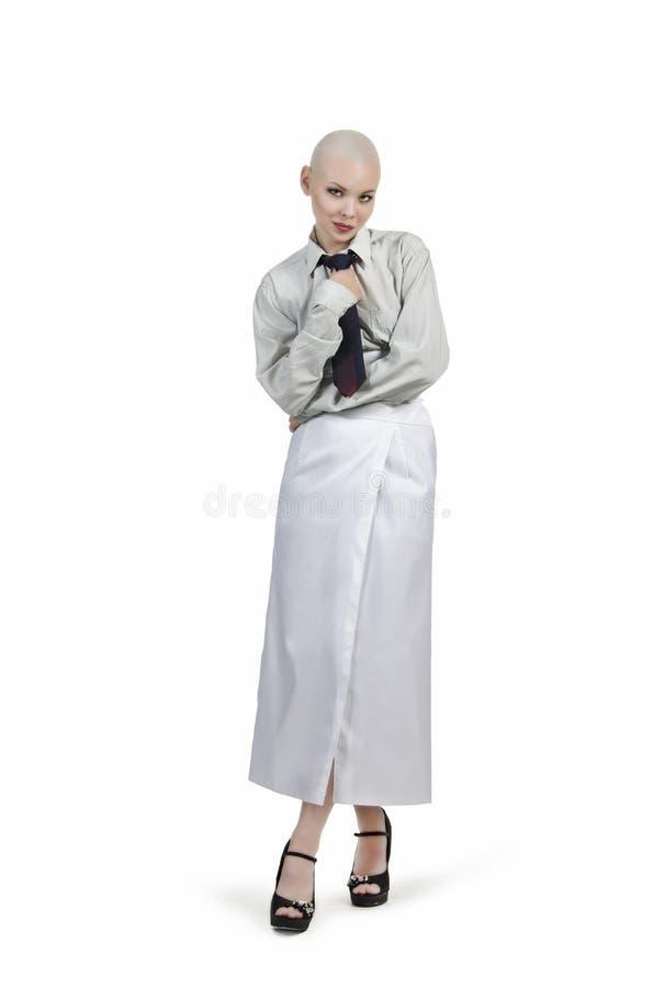 Emocjonalny portret dziewczyna, ogolony łysy, w lekkiej koszula z krawatem i białą spódnicą zdjęcia royalty free