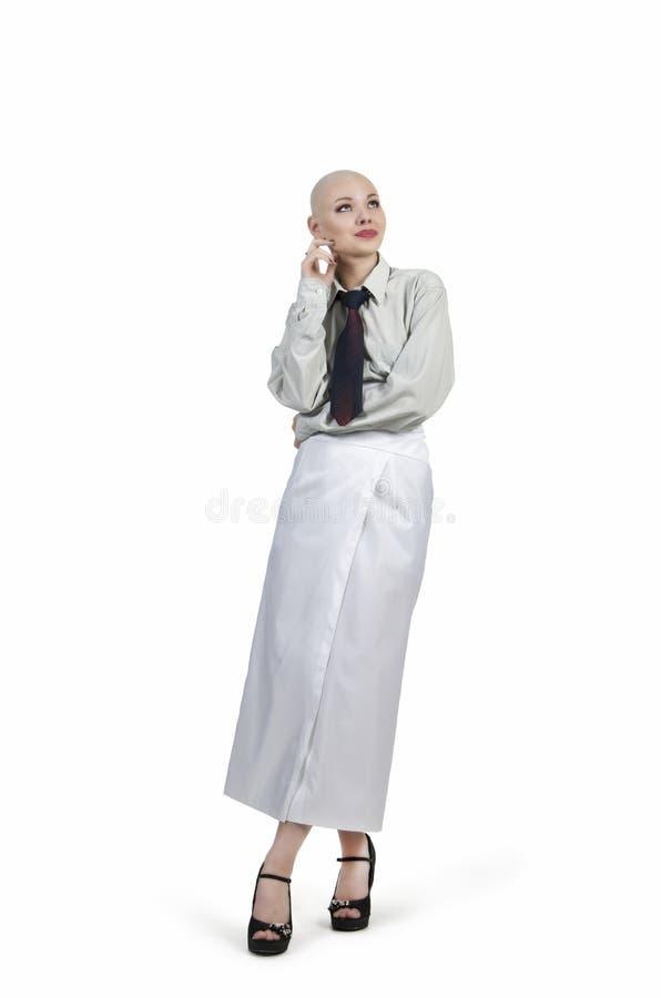 Emocjonalny portret dziewczyna, ogolony łysy, w lekkiej koszula z krawatem i białą spódnicą obrazy royalty free