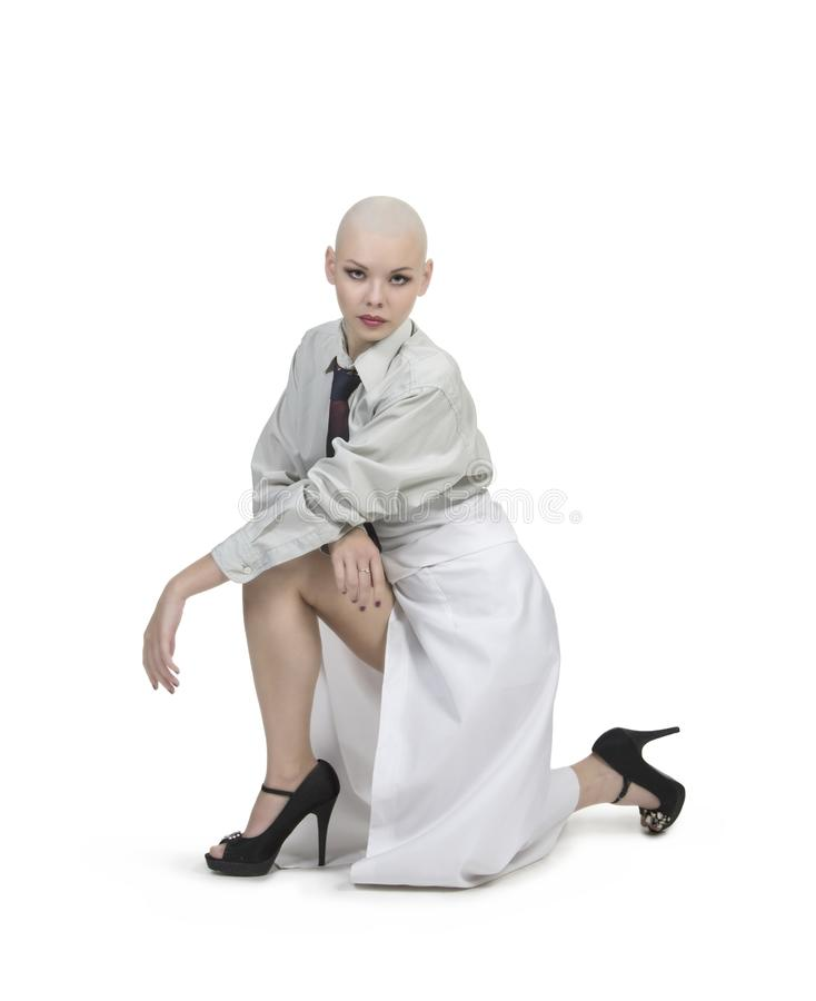 Emocjonalny portret dziewczyna, ogolony łysy, w lekkiej koszula z krawatem i białą spódnicą obrazy stock