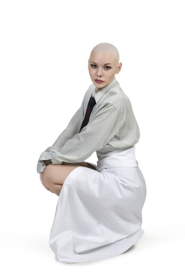 Emocjonalny portret dziewczyna, ogolony łysy, w lekkiej koszula z krawatem i białą spódnicą obraz stock