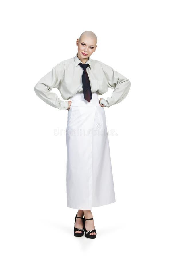 Emocjonalny portret dziewczyna, ogolony łysy, w lekkiej koszula z krawatem i białą spódnicą obraz royalty free