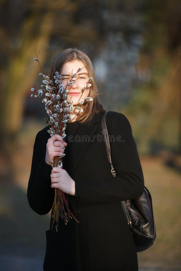 Emocjonalny portret młoda szczęśliwa piękna kobieta jest ubranym czarnego żakiet pozuje na miasto parku przy evenin z bukietem wi obraz stock