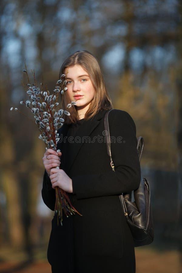 Emocjonalny portret młoda szczęśliwa piękna kobieta jest ubranym czarnego żakiet pozuje na miasto parku przy evenin z bukietem wi fotografia stock
