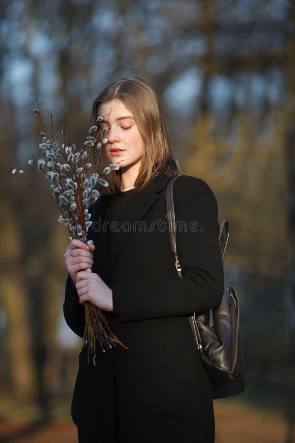 Emocjonalny portret młoda szczęśliwa piękna kobieta jest ubranym czarnego żakiet pozuje na miasto parku przy evenin z bukietem wi obrazy stock