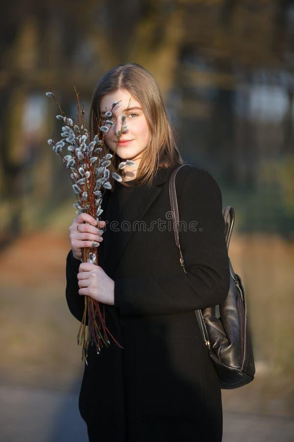 Emocjonalny portret młoda szczęśliwa piękna kobieta jest ubranym czarnego żakiet pozuje na miasto parku przy evenin z bukietem wi zdjęcie royalty free