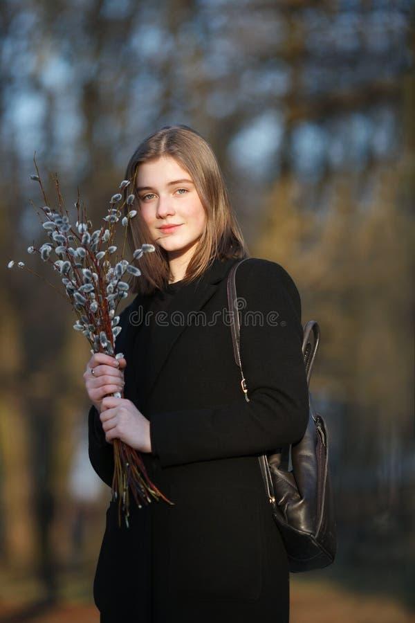 Emocjonalny portret młoda szczęśliwa piękna kobieta jest ubranym czarnego żakiet pozuje na miasto parku przy evenin z bukietem wi obrazy royalty free