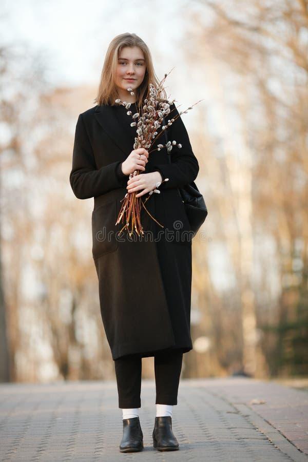 Emocjonalny portret młoda szczęśliwa piękna kobieta jest ubranym czarnego żakiet pozuje na parkowej ścieżce przy evenin z bukiete zdjęcia stock