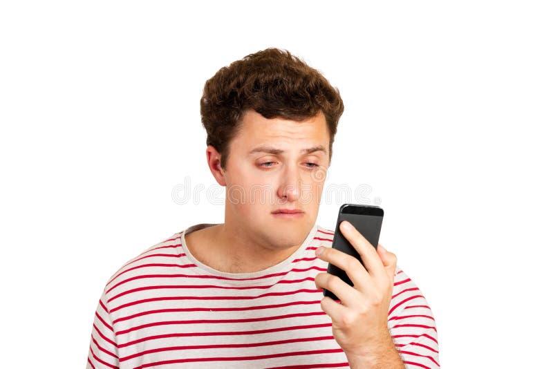 Emocjonalny portret płaczu mężczyzna patrzeje jego telefon komórkowego Czuć beznadziejność emocjonalny mężczyzna odizolowywający  fotografia royalty free