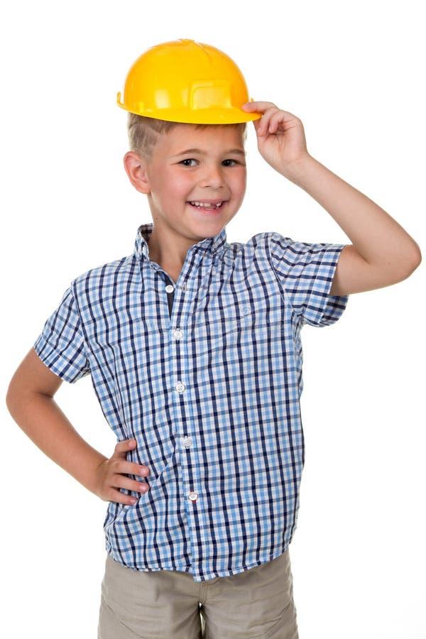 Emocjonalny portret przystojna uśmiechnięta chłopiec jest ubranym budynku żółtego ciężkiego kapelusz Śmieszny śliczny facet - inż fotografia stock