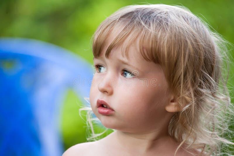 Emocjonalny widok twarzy małej białej dziewczyny na tle zielonego lata zdjęcie royalty free