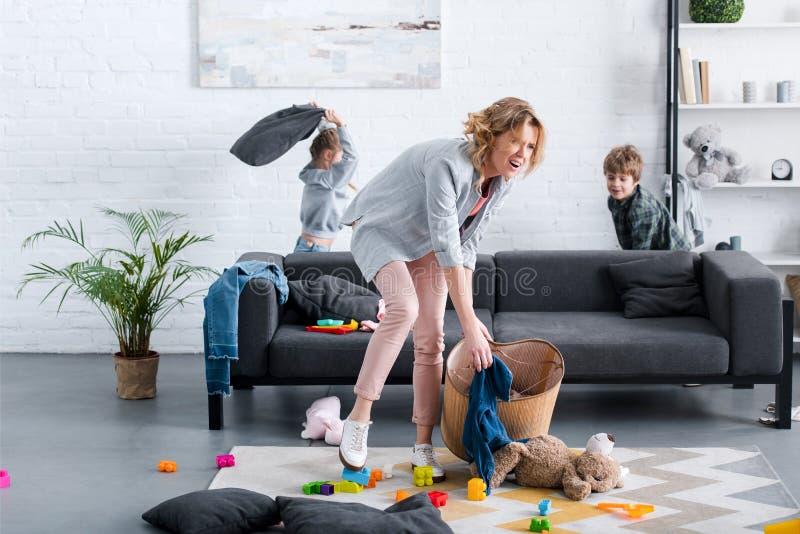emocjonalny zmęczony macierzysty kładzenie bawi się w koszu podczas gdy niegrzeczni dzieciaki ilustracji