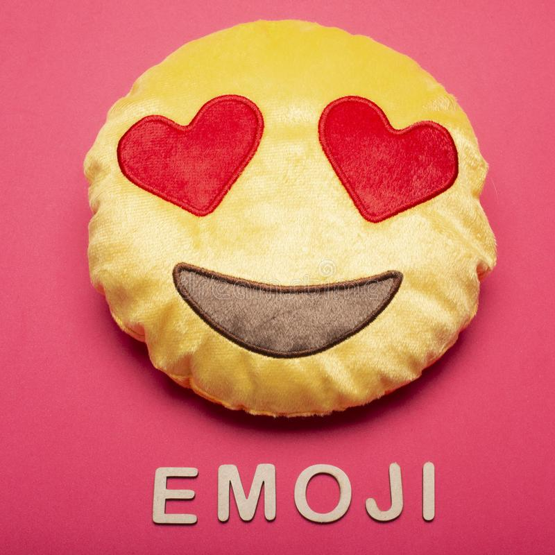 Emoji. Fabric cushion with emoji face in color background royalty free stock image