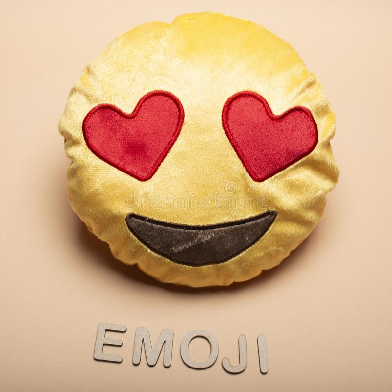 Emoji. Fabric cushion with emoji face in color background stock photo