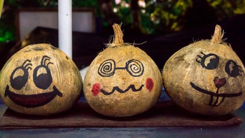 Emoji ha dipinto sulle noci di cocco vendute al mercato asiatico fotografia stock libera da diritti