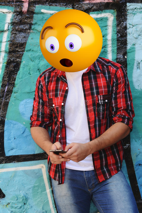 Emoji head man. Surprise emoji head man using a smartphone. Emoji concept stock photos