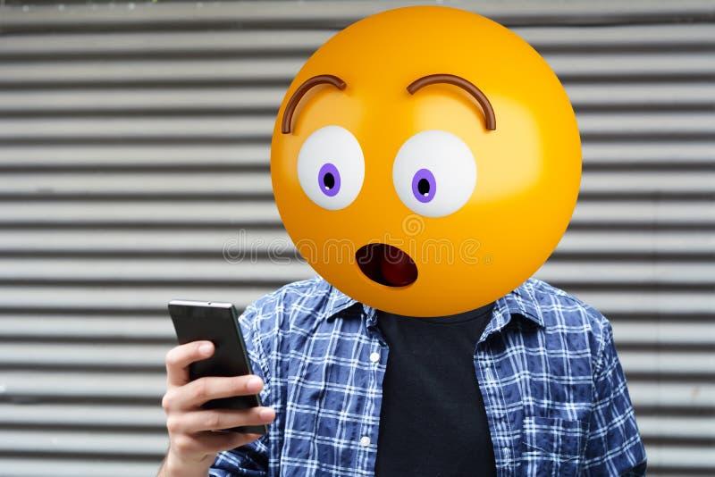 Emoji head man. Surprise emoji head man using a smartphone. Emoji concept royalty free stock image