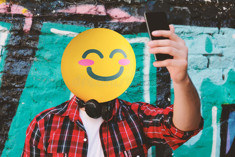 Emoji Head man taking a selfie. With his smartphone on the street royalty free stock images
