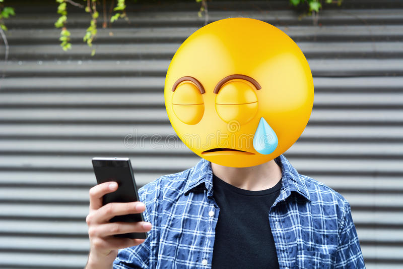 Emoji head man. Using a smartphone. Emoji concept stock photos