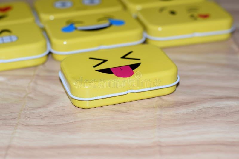 Emoji Metal Tins. Some emoji metal tins or smiley boxes, on a brown background royalty free stock image