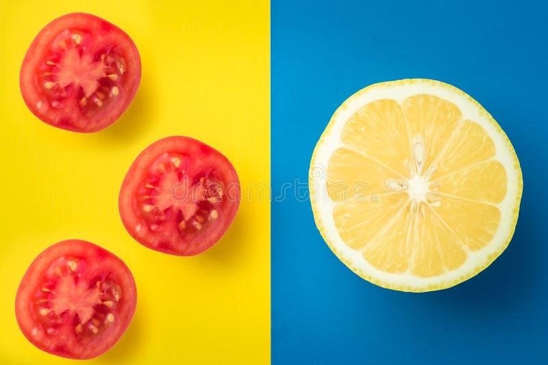 Emon на голубой предпосылке и 3 томатах вишни на желтом цвете стоковое фото rf