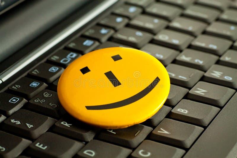 Emoticon. Smile emoticon on the laptop keyboard stock photo