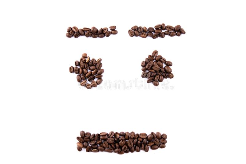 Emoticon face made of coffee beans on white backgroud with copyspace stock photos
