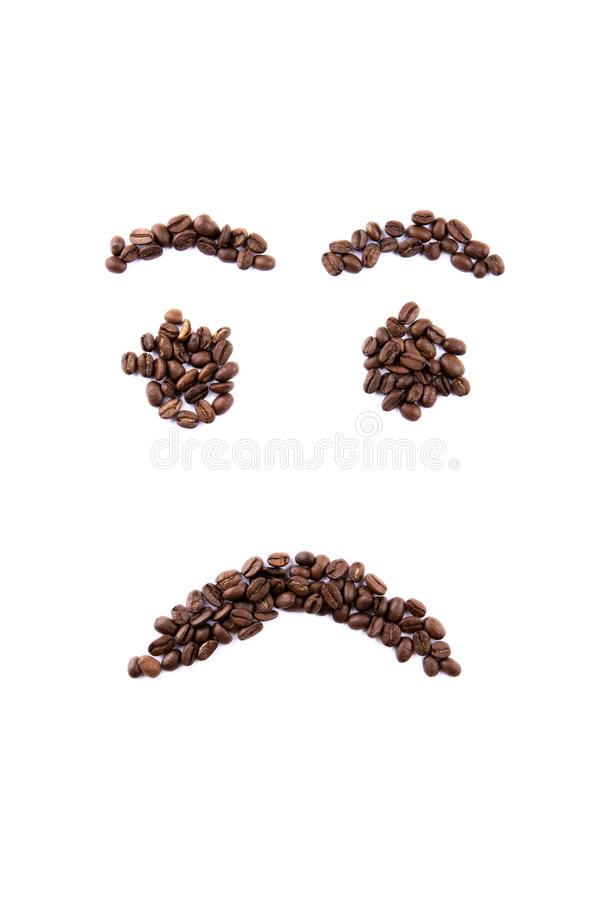 Emoticon face made of coffee beans on white backgroud with copyspace royalty free stock photos