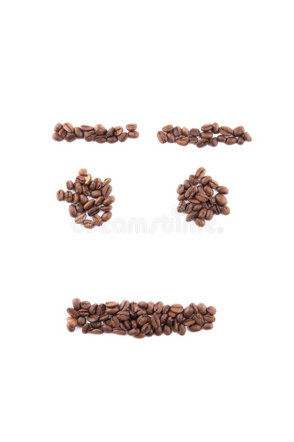 Emoticon face made of coffee beans on white backgroud with copyspace stock photography