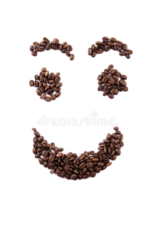 Emoticon face made of coffee beans on white backgroud with copyspace royalty free stock photo