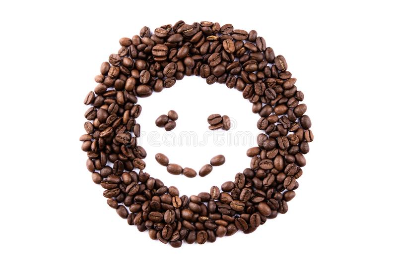 Emoticon face made of coffee beans on white backgroud with copyspace royalty free stock image