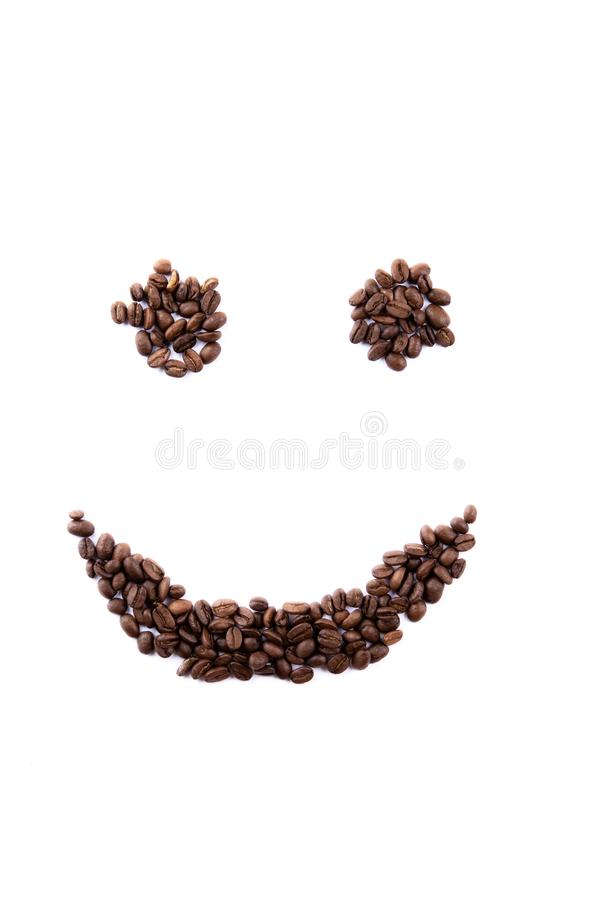 Emoticon face made of coffee beans on white backgroud with copyspace stock photo