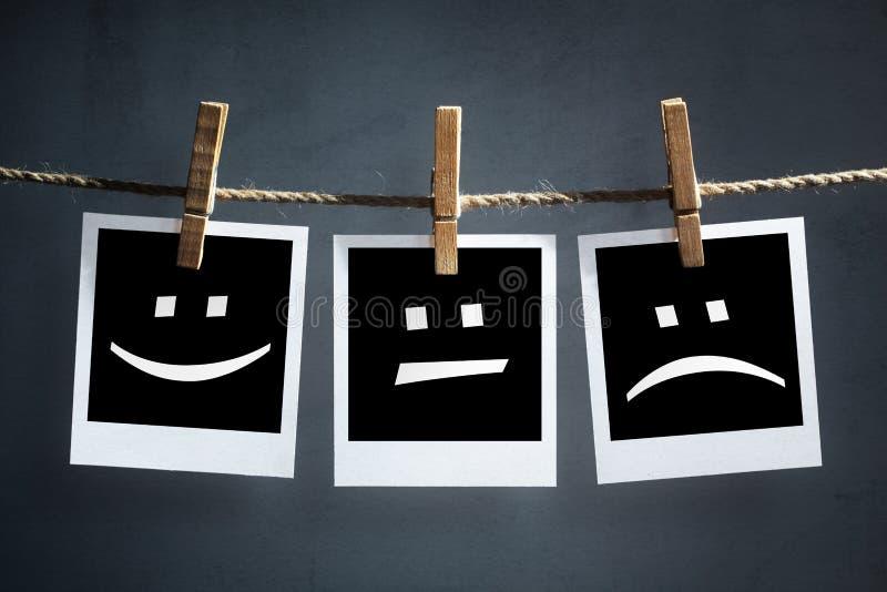 Emoticon felici, tristi e neutrali sulle fotografie istantanee della stampa fotografia stock