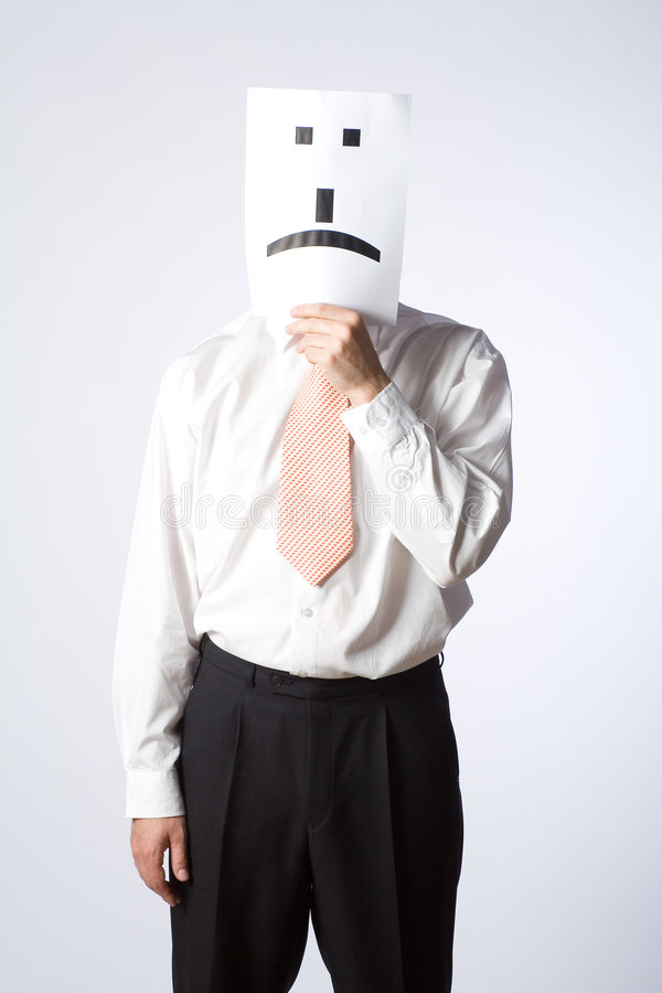 Emoticon man. A man in business attire holds up an internet emoticon for a scowl, covering his face with the emoticon stock image