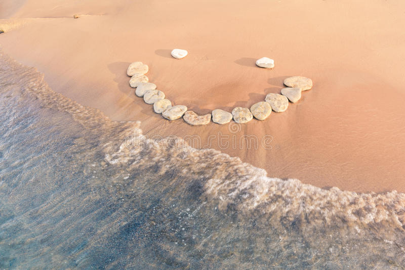 Emoticon. Of pebbles on the sandy seashore stock photography