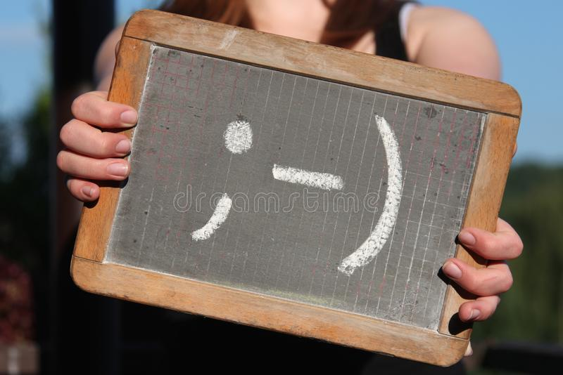 Emoticon. Sketched with chalk on slate shown by young female stock photos