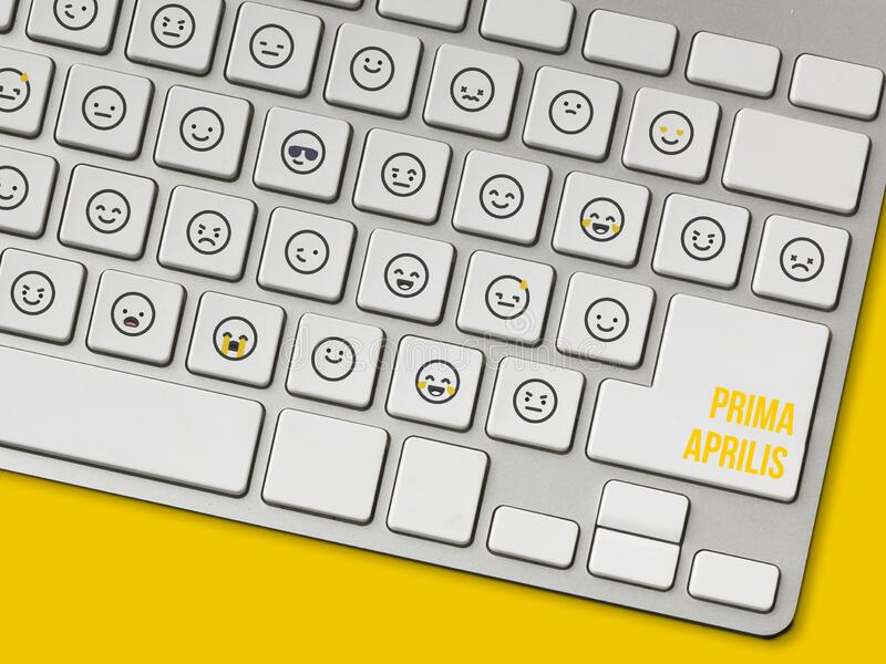 Emoticons on the keyboard for April Fools` Day. Funny emotes on a modern keyboard for April Fools` Day. Nice joke in the office to start the day. Yellow royalty free stock images