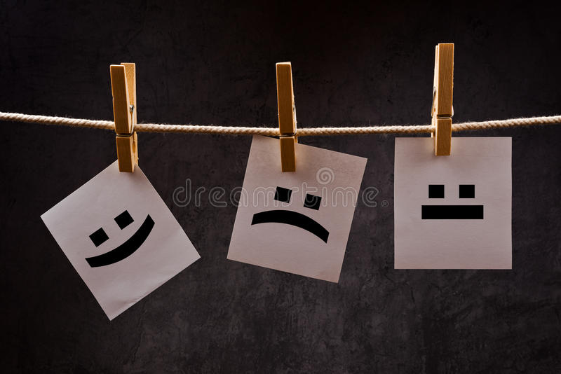 Emoticons on note paper attched to rope with clothes pins. Emoticons printed on note paper attched to rope with clothes pins - happy, sad and neutral stock images