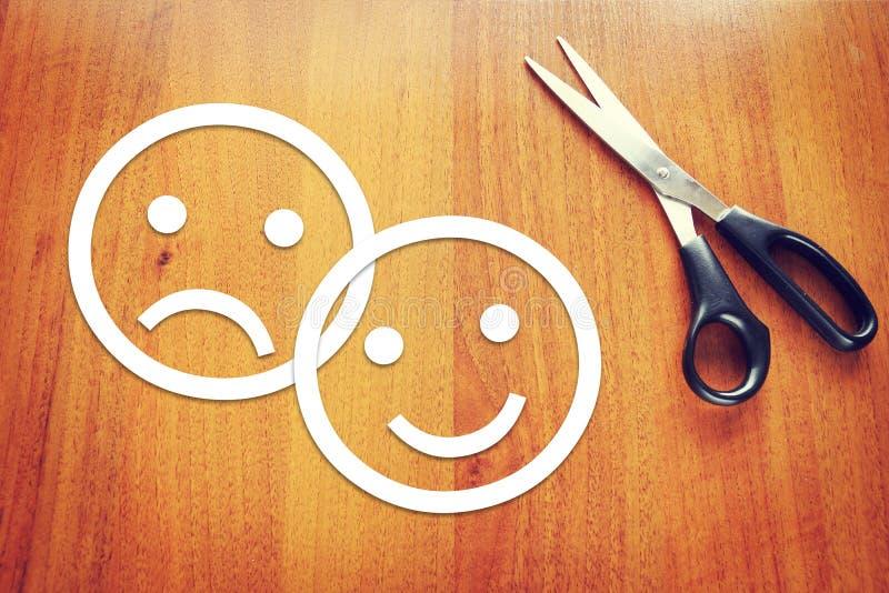 Emoticons tristes y felices hechos del papel en el escritorio fotografía de archivo libre de regalías