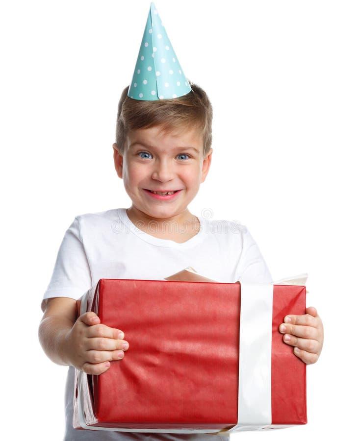 emoties Een kleine jongen met een glimlach en een gift in zijn handen Witte geïsoleerde achtergrond stock fotografie