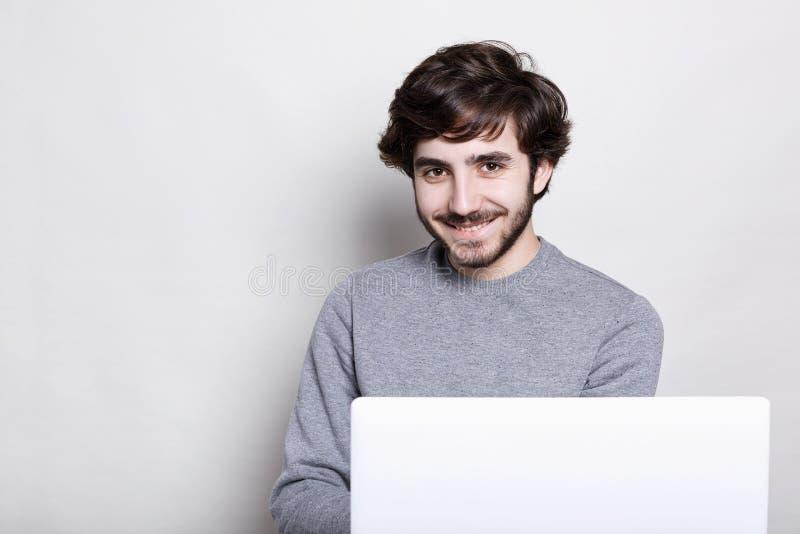 Emoties, menselijk, modern technologieën en levensstijlconcept Gelukkige aantrekkelijke jonge gebaarde kerel die van vrije draadl stock fotografie