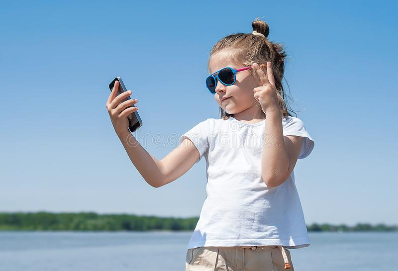 Emoties, uitdrukkingen en mensenconcept - gelukkige jong kind of tiener die selfie met smartphone over blauwe hemel nemen royalty-vrije stock foto's