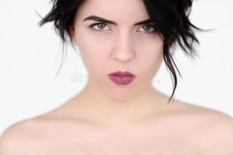 Emotion face grumpy offended pursed lips woman. Emotion face. grumpy offended woman with pursed lips and piercing glance. young beautiful brunette girl portrait stock photography