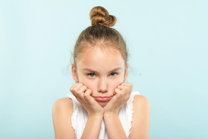 Emotion face grumpy pursed lips frowning child. Emotion face. frowning grumpy child with pursed lips and sad look. young cute girl portrait on blue background royalty free stock images