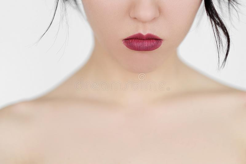 Emotion face pursed sad woman lips. Emotion face. pursed sad woman lips. perfect skin decollete and dark lipstick. young brunette girl on white background royalty free stock images