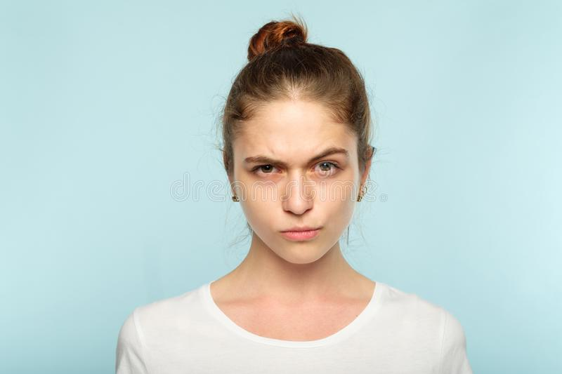 Emotion frowning face grumpy pursed lips woman. Emotion face. frowning grumpy woman with pursed lips and piercing glance. young beautiful brown haired girl stock photos
