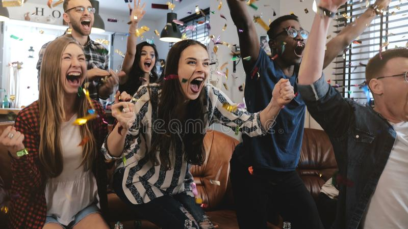 Emotion. Multi-ethnic fans celebrate winning. Confetti 4K slow motion. Passionate supporters shout watching game on TV. Emotion. Multi-ethnic fans celebrate stock photo