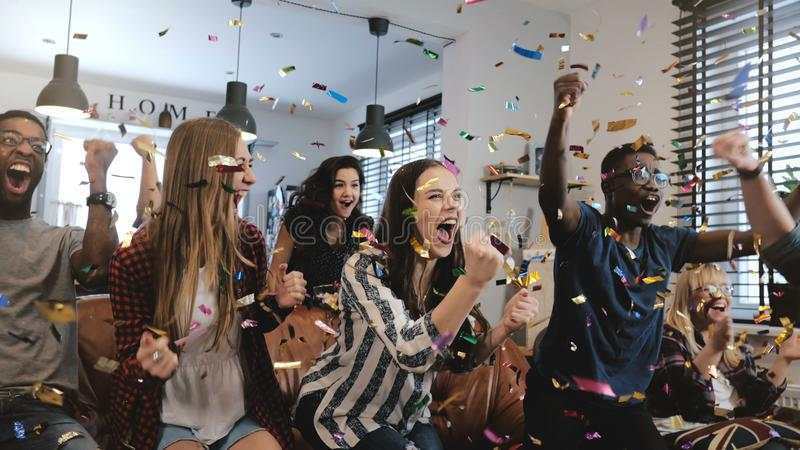 Emotion. Multi-ethnic fans celebrate winning. Confetti 4K slow motion. Passionate supporters shout watching game on TV. Emotion. Multi-ethnic fans celebrate royalty free stock image