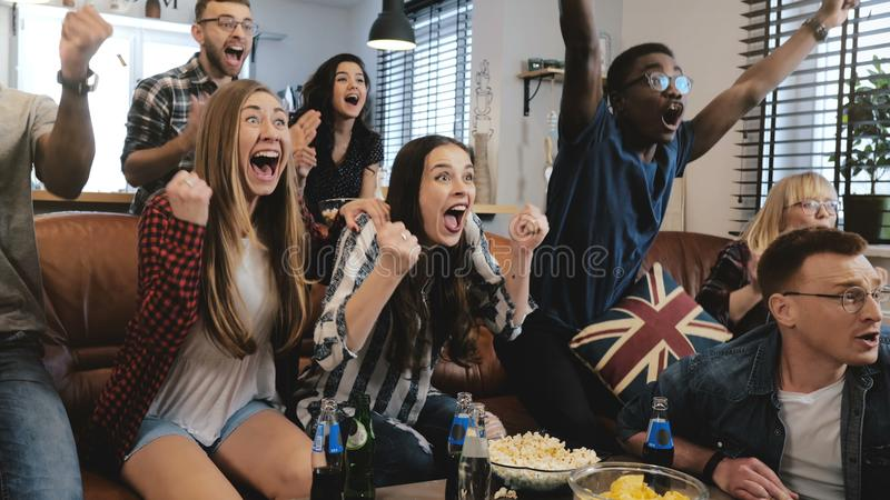 Emotion. Multi-ethnic fans celebrate winning. Confetti 4K slow motion. Passionate supporters shout watching game on TV. Emotion. Multi-ethnic fans celebrate stock photography