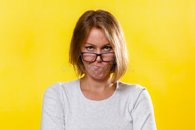 Emotion och psykologi Kvinnan, en blond med glasögon, korsade hennes armar och snörpte hennes läppar med ett missnöjt ansikte arkivbilder